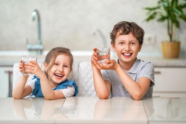 I bambini piccoli divertenti bevono l'acqua nella cucina di casa