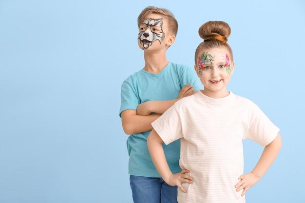 Piccoli bambini divertenti con pittura del viso sul colore