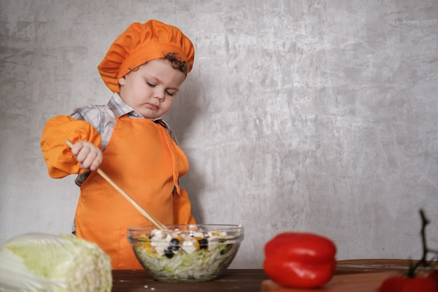 Divertente ragazzino europeo vestito come uno chef mescola un'insalata greca con un cucchiaio in una ciotola