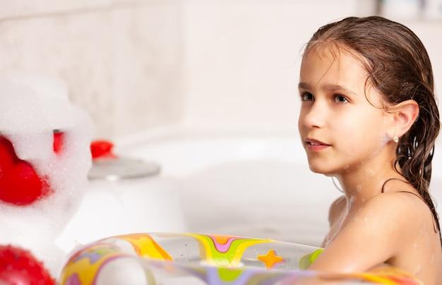 La bambina divertente bagna in una vasca da bagno con un salvagente gonfiabile