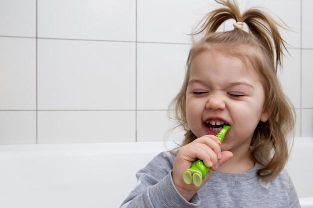 La bambina divertente si lava i denti in bagno. concetto di cure odontoiatriche