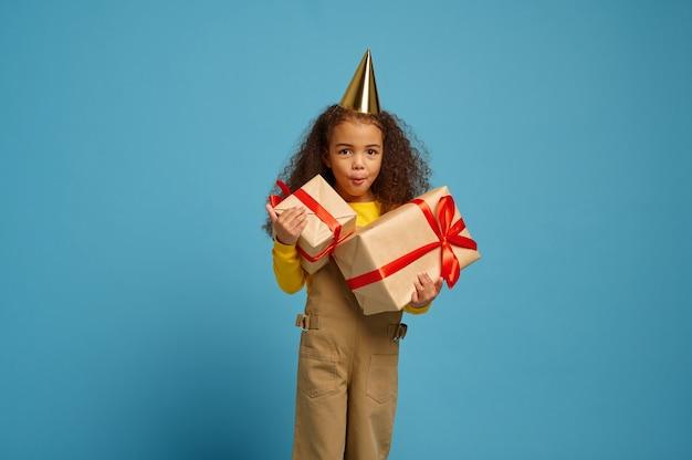 La bambina divertente in protezione tiene il contenitore di regalo di compleanno con i nastri rossi, fondo blu. bel bambino ha ricevuto una sorpresa, celebrazione dell'evento