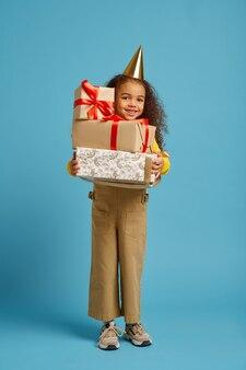 La bambina divertente in protezione tiene il contenitore di regalo di compleanno con i nastri rossi, fondo blu. il bel bambino ha avuto una sorpresa