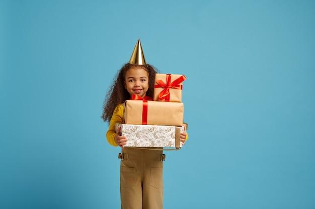 La bambina divertente in protezione tiene il contenitore di regalo di compleanno con i nastri rossi. bel bambino ha ricevuto una sorpresa, celebrazione dell'evento