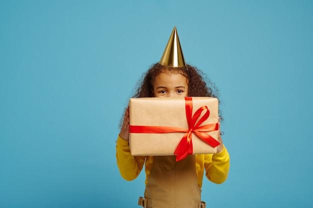 La bambina divertente in protezione tiene il contenitore di regalo di compleanno con i nastri rossi. il bel bambino ha avuto una sorpresa