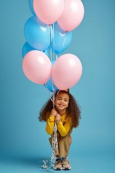 La bambina divertente in berretto tiene un mazzo di palloncini colorati, sfondo blu. il bel bambino ha ricevuto una sorpresa, un evento o una festa di compleanno