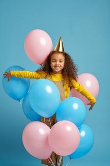 La bambina divertente in berretto tiene un mazzo di palloncini colorati, sfondo blu. bel bambino ha ricevuto una sorpresa, un evento o una festa di compleanno birthday