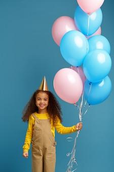 La bambina divertente in berretto tiene un mazzo di palloncini colorati. il bel bambino ha ricevuto una sorpresa, un evento o una festa di compleanno
