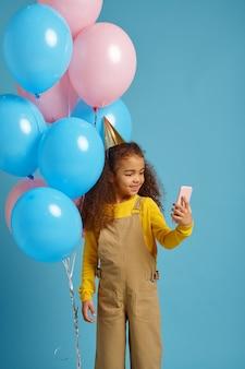 La bambina divertente in berretto fa selfie con un mazzo di palloncini colorati. il bel bambino ha ricevuto una sorpresa, un evento o una festa di compleanno