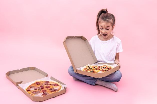 Bambina divertente deliziata con la pizza in una scatola per la consegna, sfondo rosa.