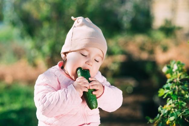 Bambina divertente che mangia cetriolo fresco in giardino in primavera