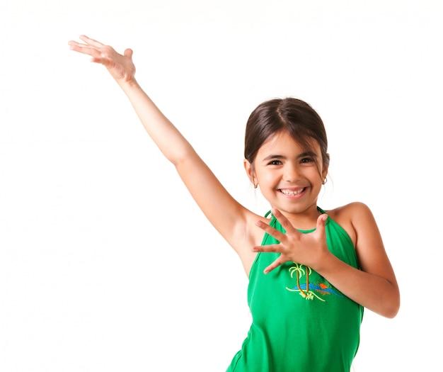 La bambina divertente in vestito verde ondeggia la sua mano