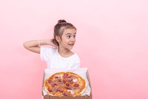La bambina divertente guarda pensierosa la pizza in una scatola, sfondo rosa, copia spazio.