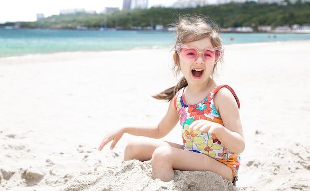 Bambina divertente che posa in occhiali da sole che giocano con la sabbia sulla spiaggia. divertimento estivo e ricreazione.