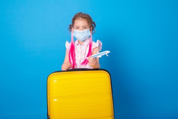 Bambina divertente in maschera protettiva con aereo giocattolo e valigia gialla sulla superficie blu.