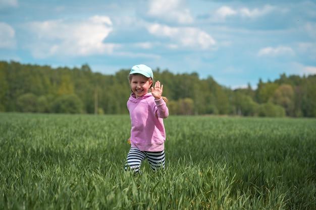 La bambina divertente passa il campo con i tiri verdi del grano in campagna
