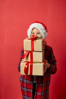 Bambina divertente in cappello della santa con molti contenitori di regalo di natale isolati su fondo rosso,