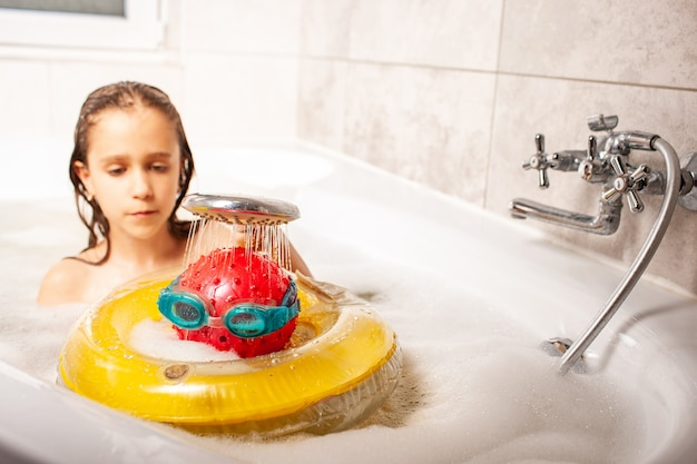 Bambina divertente che fa la doccia una testa fatta di una palla e occhiali da nuoto da