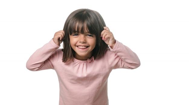Bambina divertente che mostra la lingua alla macchina fotografica su fondo bianco