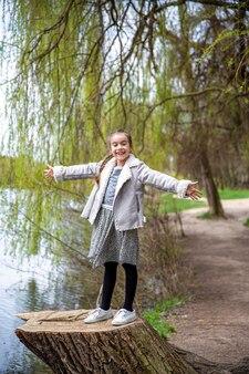Una bambina divertente in una passeggiata nella foresta primaverile gode della natura.