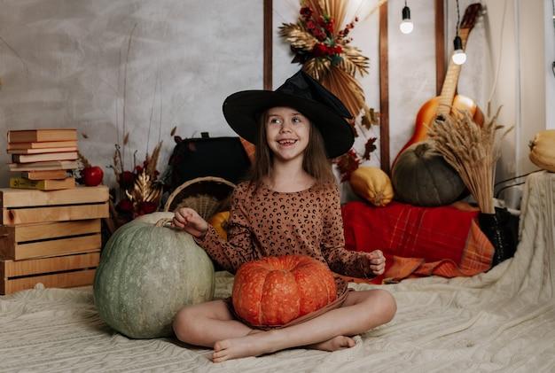Una bambina divertente con un cappello da strega è seduta su una coperta a maglia con zucche