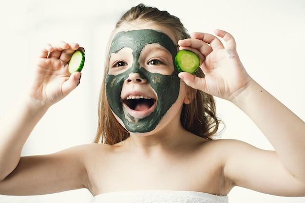 Bambina divertente con una maschera cosmetica fatta di argilla