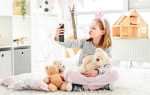Bambina divertente con l'orsacchiotto che prende selfie nella stanza accogliente