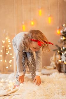 Una ragazzina divertente con le corna che salta sul letto su uno sfondo di decorazioni e luci natalizie. buone vacanze invernali