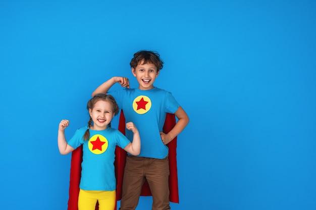 Divertimento super eroe per bambini divertenti in impermeabili e maschera rossi.
