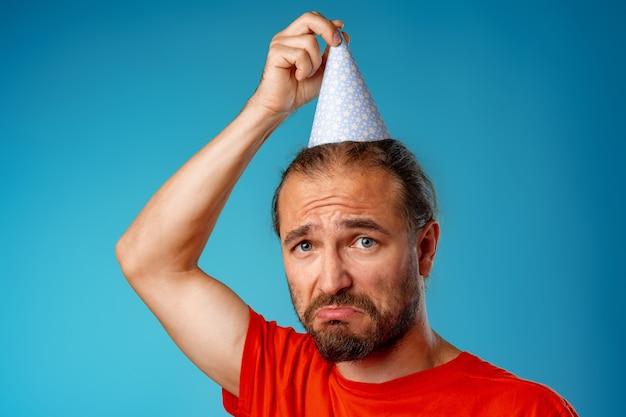 Uomo barbuto dai capelli lunghi divertente nel cono di partito su sfondo blu