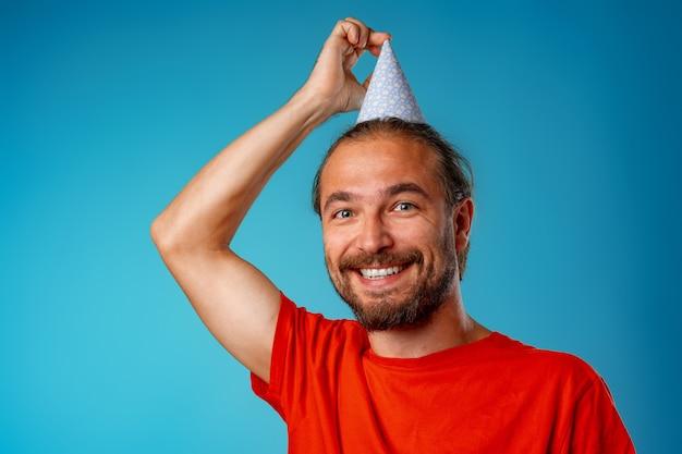 Uomo barbuto dai capelli lunghi divertente nel cono del partito