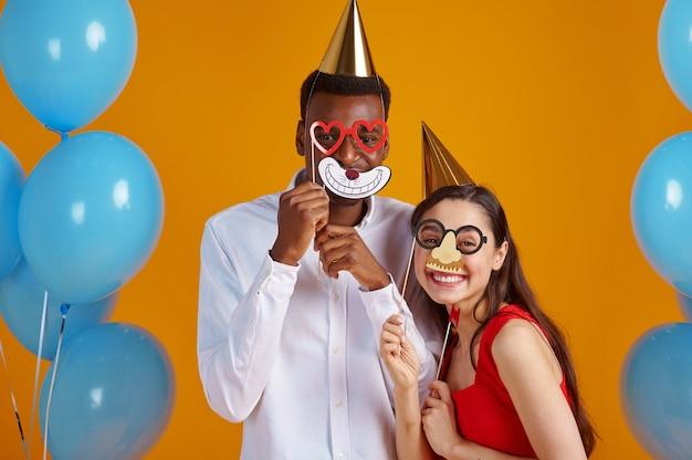 Coppia d'amore divertente in cappellini e maschere da festa. bella famiglia, evento o festa di compleanno, decorazione di palloncini