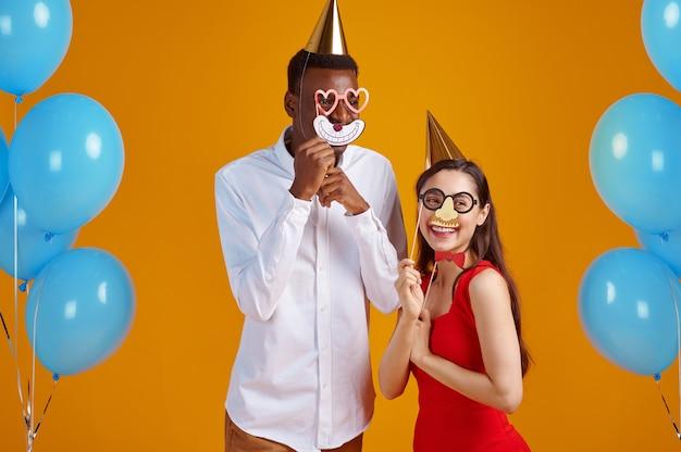 Coppia d'amore divertente in berretti e maschere da festa, sfondo giallo. bella famiglia, evento o festa di compleanno, decorazione di palloncini