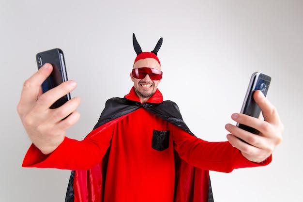 Uomo divertente in mantello di halloween rosso nero, occhiali da sole e cappello con le corna che prendono selfie con lo smartphone sopra il fondo bianco dello studio.
