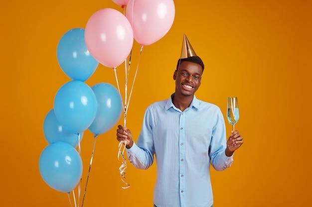 Uomo divertente in berretto che tiene un bicchiere di bevanda, sfondo giallo. la persona di sesso maschile sorridente ha ricevuto una sorpresa, un evento o una festa di compleanno, una decorazione di palloncini