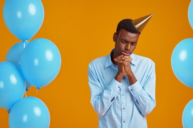 Uomo divertente in berretto. la persona di sesso maschile ha ricevuto una sorpresa, un evento o una festa di compleanno, una decorazione di palloncini blu