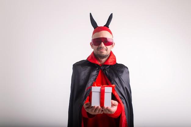 Uomo divertente in costume di halloween e giftbox isolato su bianco.