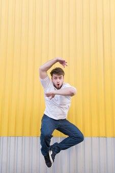 Uomo divertente che salta contro il muro giallo