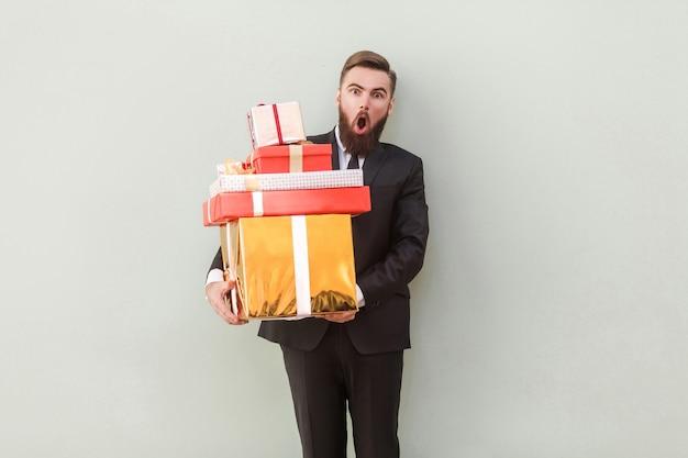 Uomo divertente che guarda l'obbiettivo con la faccia scioccata e tiene scatole regalo. colpo dello studio. isolato su sfondo grigio