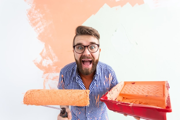 Uomo divertente pittura parete interna con rullo di vernice nella nuova casa