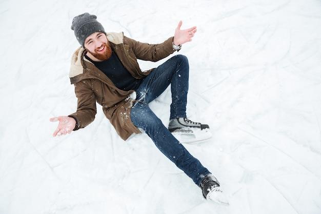 Uomo divertente seduto sulla neve con i pattini da ghiaccio