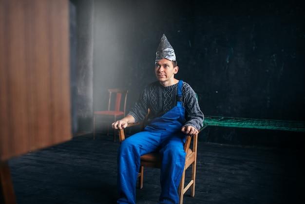 Uomo divertente in cappello di carta stagnola si siede sulla sedia, concetto di paranoia. ufo, teoria del complotto, protezione dal furto di cervello, fobia