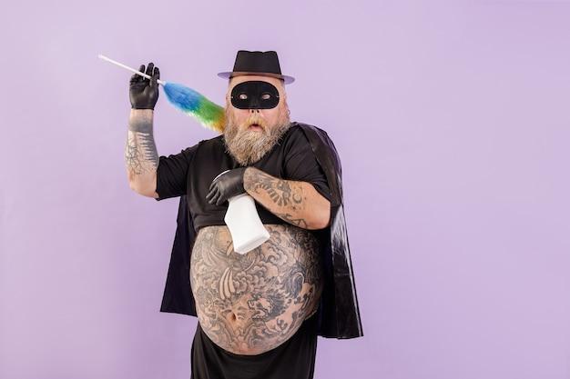 Uomo divertente con sovrappeso in costume da eroe con pennello e detersivo su sfondo viola