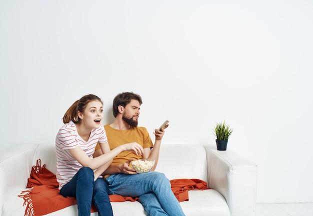 Uomo e donna divertenti a casa sul divano riposano popcorn
