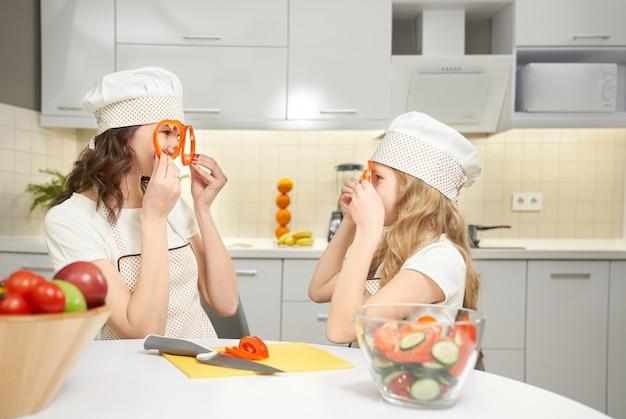 Fette divertenti del pepe della tenuta della figlia e della mamma come vetri.