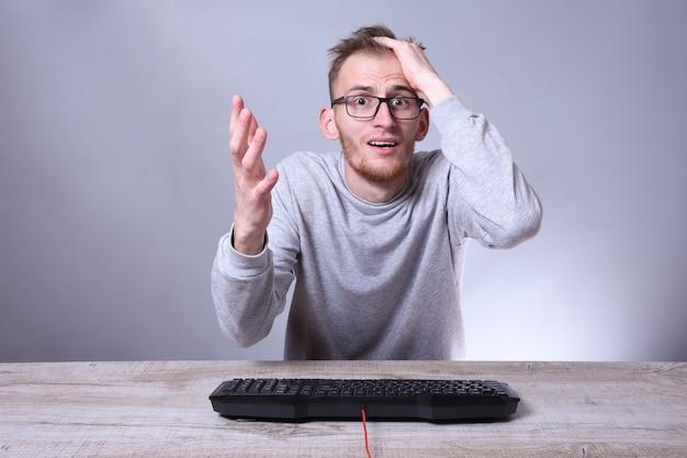 Giovane uomo d'affari divertente del nerd, uomo che lavora al computer