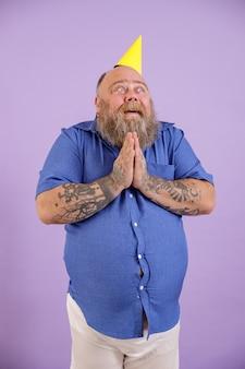 La persona maschio obesa divertente si tiene per mano nel gesto di preghiera su fondo porpora