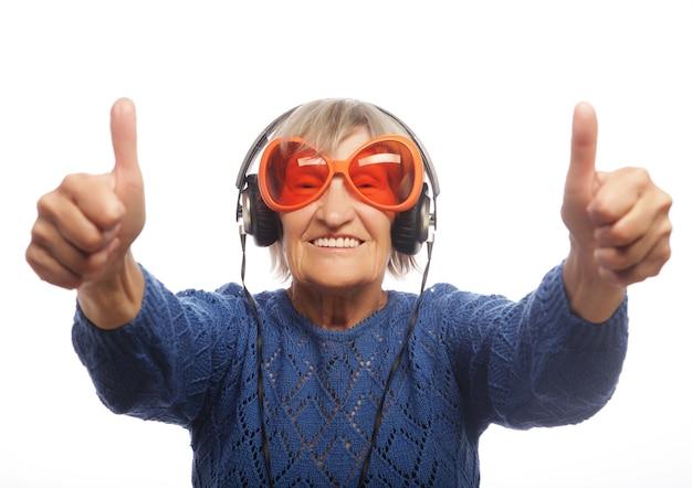 Divertente vecchia signora ascoltando musica e mostrando i pollici in su. isolato su bianco.
