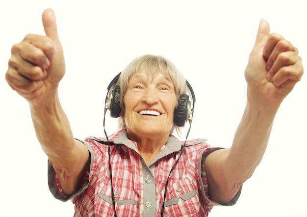 Musica d'ascolto della signora anziana divertente e che mostra i pollici su. isolato su bianco.