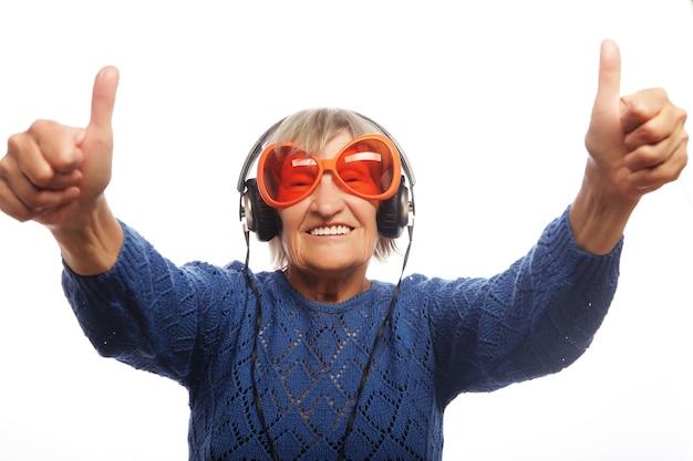 Divertente vecchia signora ascoltando musica e mostrando i pollici in su isolato